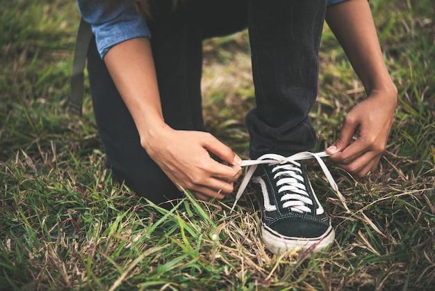 Jeune femme backpacker tout nouage lacets de chaussures de randonnée vont à la forêt. Photo gratuit