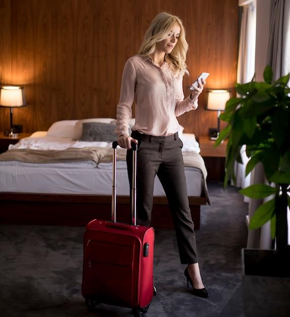 Jeune femme avec des bagages dans la chambre d'hôtel Photo Premium