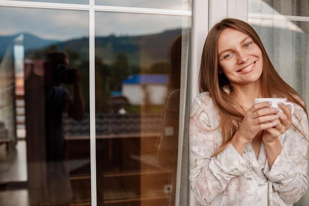 Jeune Femme Sur Le Balcon Tenant Une Tasse De Café Ou De Thé Le Matin. Femme Est Vêtue De Vêtements De Nuit élégants. Temps De Repos. Photo Premium