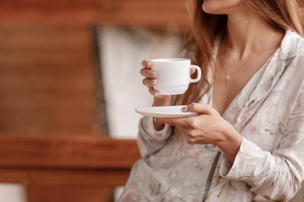 Jeune Femme Sur Le Balcon Tenant Une Tasse De Café Ou De Thé Le Matin. Photo Premium