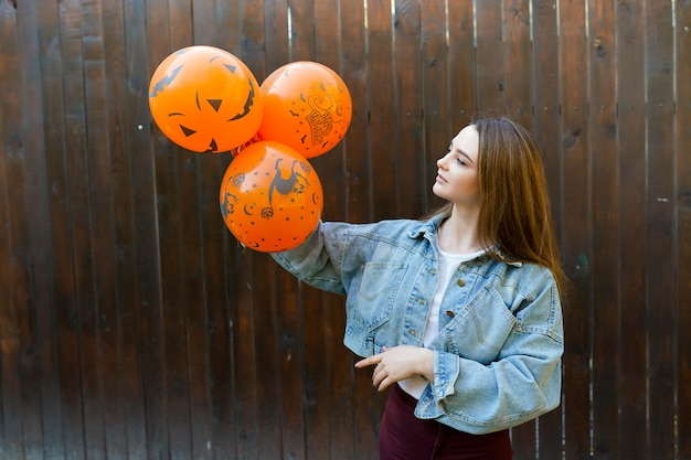 Jeune femme avec des ballons orange gonflables halloween sur fond marron Photo Premium