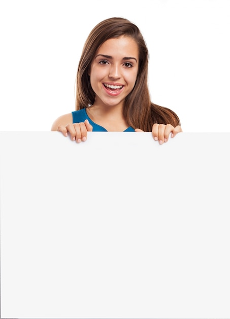 Jeune femme avec un beau sourire posant avec une affiche vide Photo gratuit