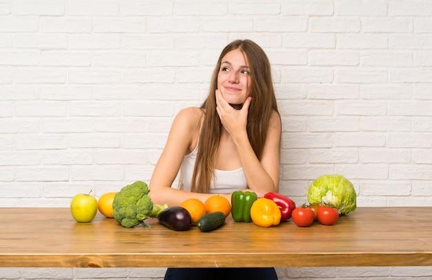 Jeune femme avec beaucoup de légumes pense à une idée Photo Premium