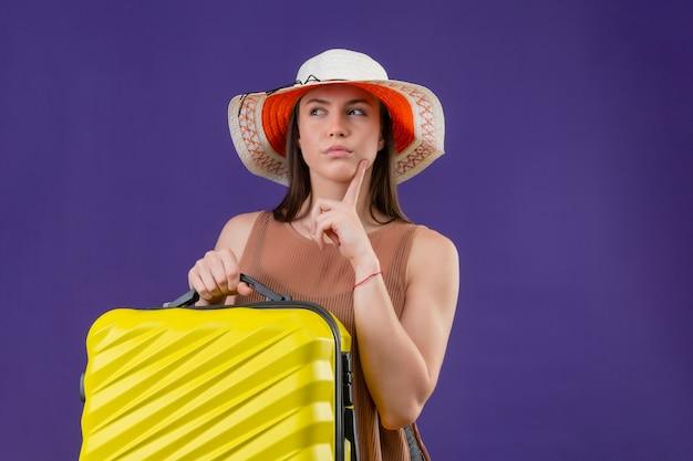 Jeune Femme Belle Voyageur En Chapeau D'été Avec Valise Jaune à Côté Avec Le Doigt Près De La Pensée Du Menton Photo gratuit