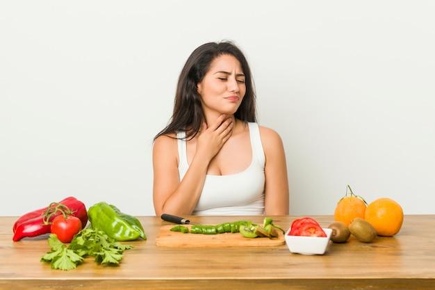 Une jeune femme bien préparée qui prépare un repas sain a mal à la gorge à cause d'un virus ou d'une infection. Photo Premium