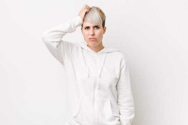 Jeune femme bien roulée portant un chandail à capuchon blanc, sous le choc, elle s'est souvenue d'une réunion importante. Photo Premium
