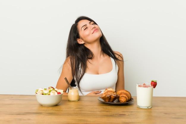 Jeune femme bien roulée prenant son petit-déjeuner touche le ventre, sourit doucement, concept de restauration et de satisfaction. Photo Premium