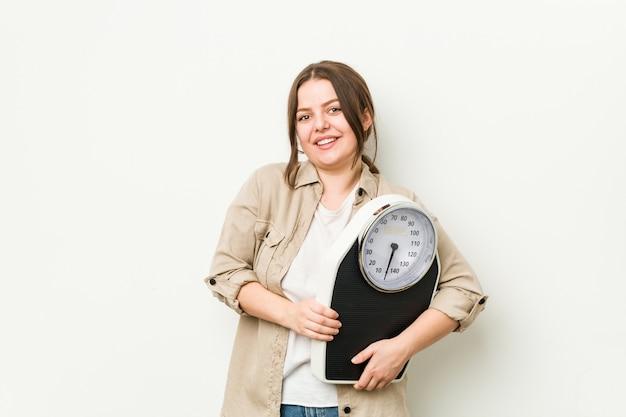 Jeune Femme Bien Roulée Tenant Une Balance En Riant Et En S'amusant. Photo Premium