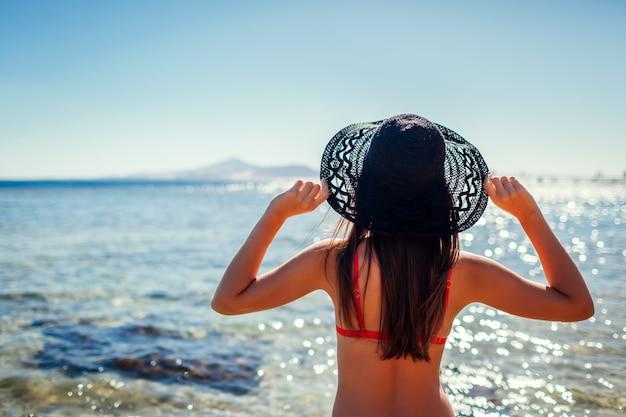 Jeune femme en bikini tenant un chapeau sur la plage en mer rouge. concept de voyage et de vacances Photo Premium