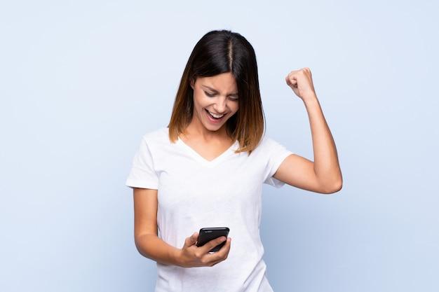 Jeune femme sur bleu isolé à l'aide de téléphone portable Photo Premium