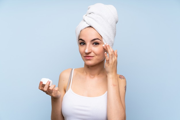 Jeune femme sur bleu isolé avec crème hydratante Photo Premium