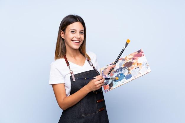 Jeune femme sur bleu isolé tenant une palette Photo Premium