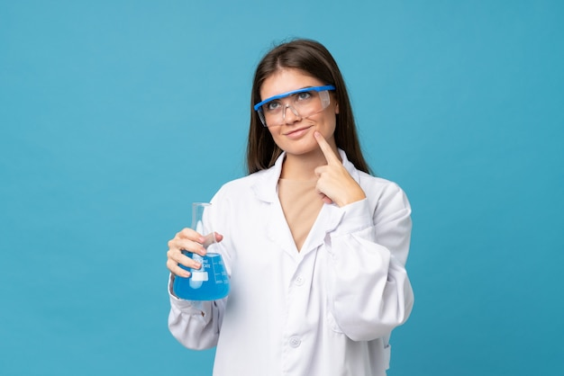 Jeune femme sur bleu isolé avec un tube à essai scientifique Photo Premium