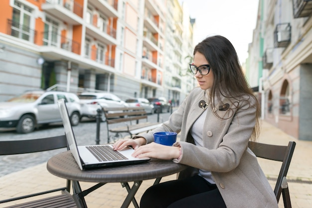 Jeune Femme Blogueuse Dans Un Café En Plein Air Avec Ordinateur Photo Premium