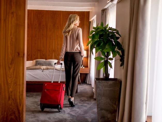 Jeune femme blonde arrive dans une chambre d'hôtel avec valise rouge Photo Premium