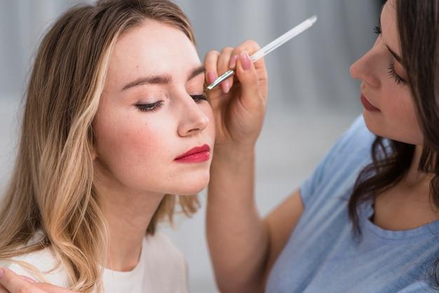 Jeune femme blonde et artiste se maquillant les yeux Photo gratuit