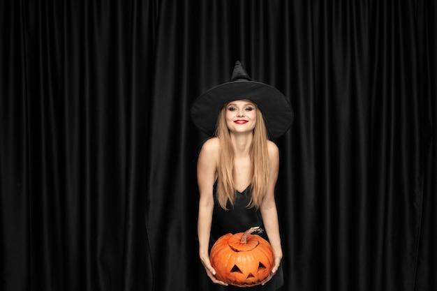 Jeune Femme Blonde Au Chapeau Noir Et Costume Sur Fond Noir. Modèle Féminin Attrayant Et Sensuel. Halloween, Vendredi Noir, Cyber Lundi, Soldes, Automne Photo gratuit