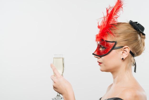 Jeune femme blonde au masque avec des plumes rouges, tenant le verre Photo gratuit