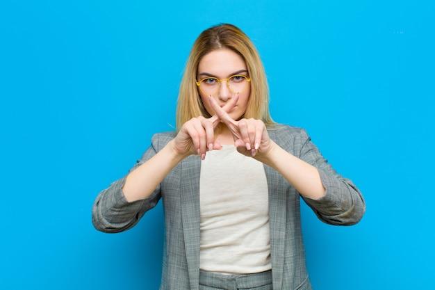 Jeune femme blonde aux airs sérieux et contrariée, les deux doigts croisés devant le rejet, demandant le silence sur le mur bleu Photo Premium