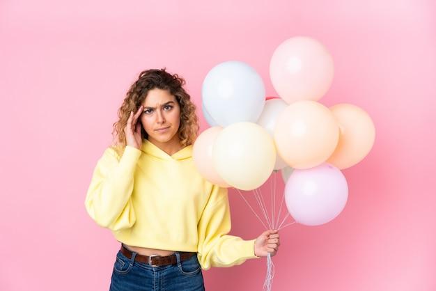 Jeune Femme Blonde Aux Cheveux Bouclés Attraper De Nombreux Ballons Sur Le Mur Rose Malheureux Et Frustré Par Quelque Chose. Photo Premium