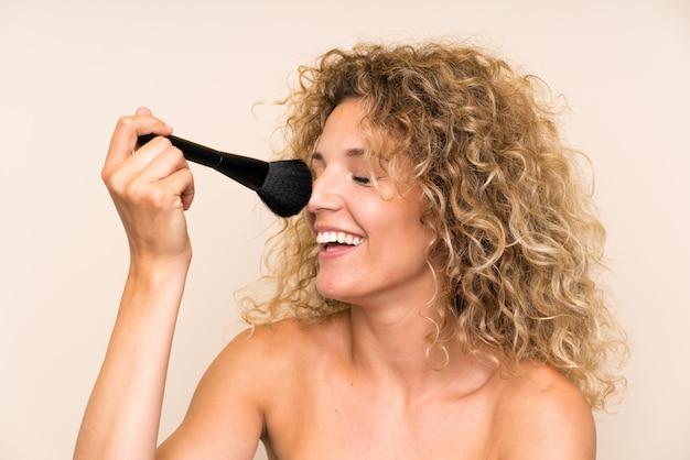 Jeune femme blonde aux cheveux bouclés avec un pinceau de maquillage Photo Premium