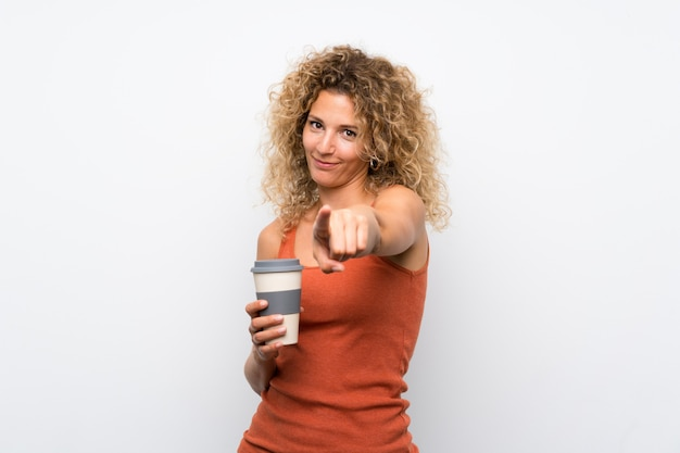 Jeune femme blonde aux cheveux bouclés tenant un café à emporter pointe le doigt sur vous avec une expression confiante Photo Premium