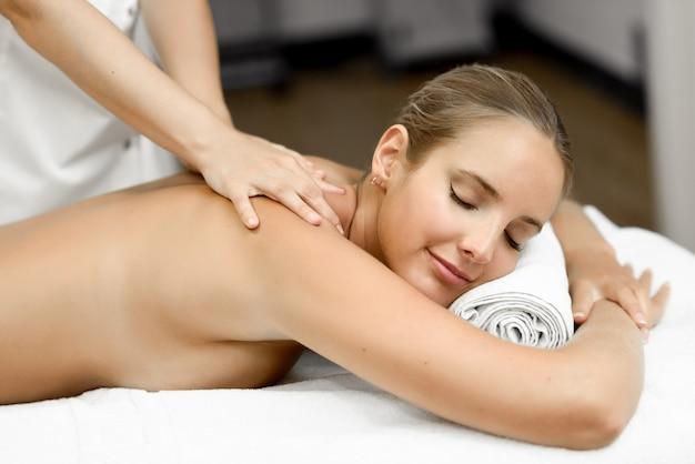 Jeune femme blonde ayant un massage et souriant dans le spa Photo gratuit
