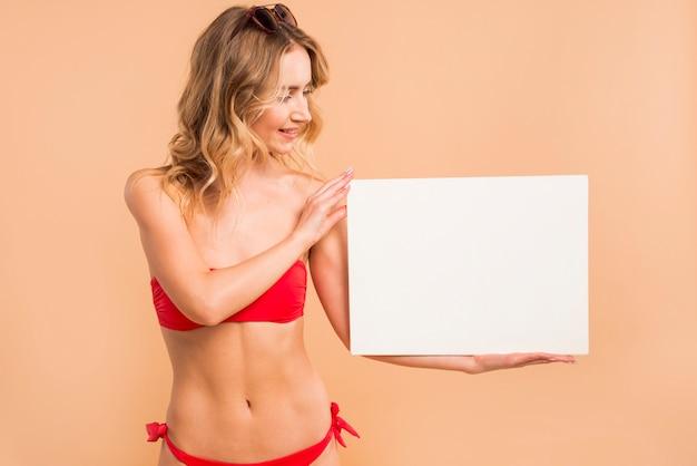 Jeune femme blonde en bikini rouge tenant une planche vierge Photo gratuit