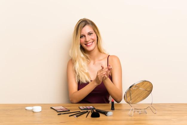 Jeune femme blonde avec cosmétique dans une table applaudissant Photo Premium
