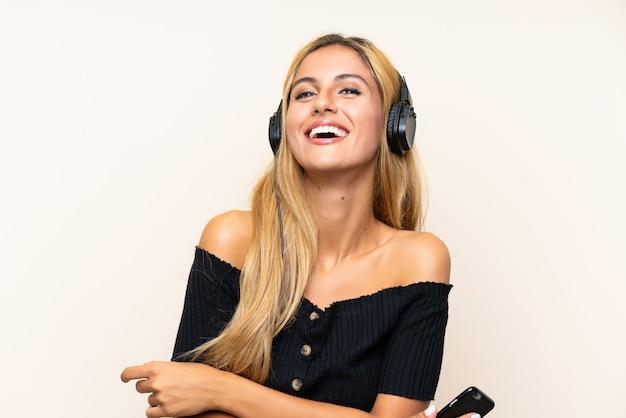 Jeune femme blonde écoute de la musique avec un téléphone portable Photo Premium