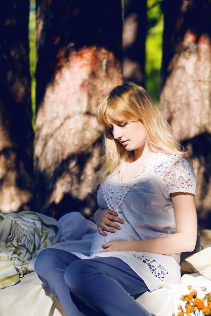 Jeune Femme Blonde Enceinte Dort Dans Un Lit Dans La Nature. Le Concept D'un Bon Sommeil Photo Premium