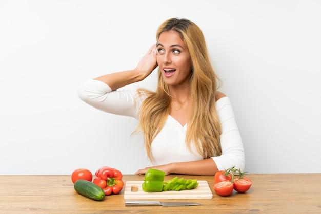 Jeune femme blonde avec des légumes dans une table en écoutant quelque chose Photo Premium