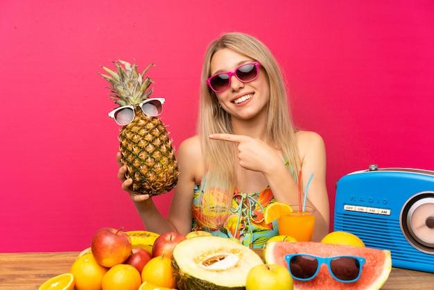 Jeune femme blonde en maillot de bain tenant un ananas avec des lunettes de soleil Photo Premium