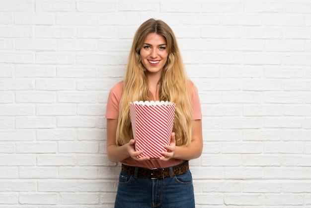 Jeune femme blonde sur le mur de briques blanches tenant un bol de pop-corn Photo Premium