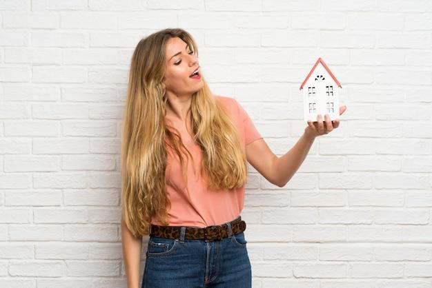 Jeune femme blonde sur le mur de briques blanches tenant une petite maison Photo Premium