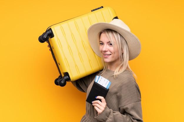 Jeune Femme Blonde Sur Un Mur Jaune Isolé En Vacances Avec Valise Et Passeport Photo Premium