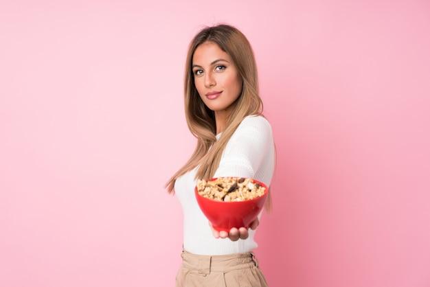 Jeune femme blonde sur un mur rose isolé, tenant un bol de céréales Photo Premium