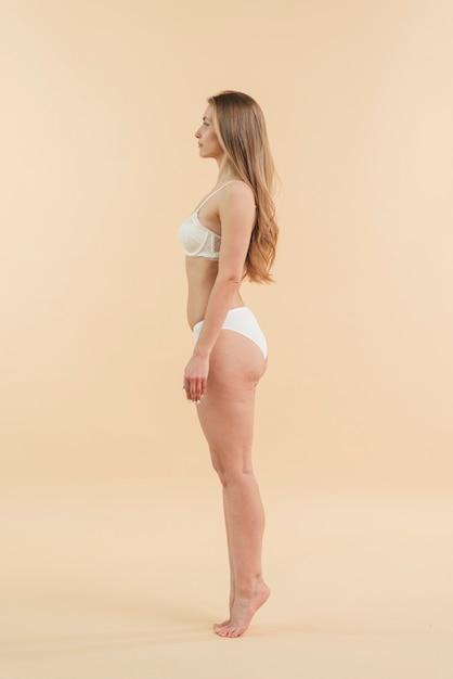 Jeune femme blonde sur la pointe des pieds qui pose en sous-vêtements Photo gratuit