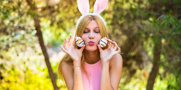 Jeune femme blonde portant des oreilles de lapin et avec des oeufs de pâques colorés et faire une blague Photo Premium