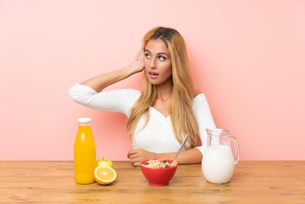 Jeune femme blonde prenant son lait petit déjeuner écoute quelque chose Photo Premium