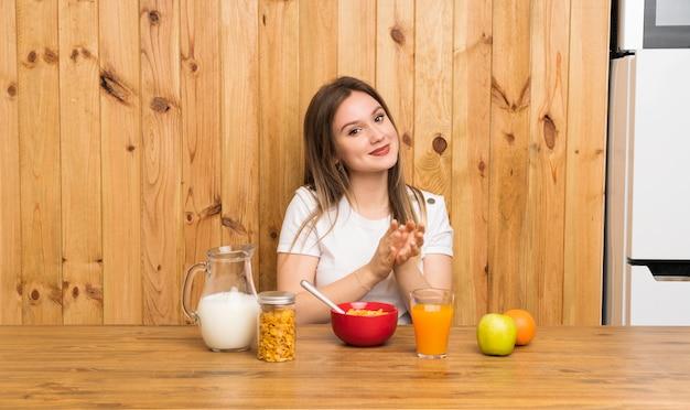 Jeune femme blonde prenant son petit déjeuner en applaudissant Photo Premium