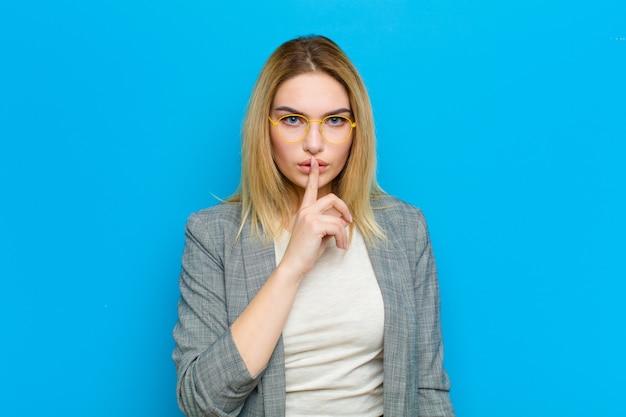 Jeune femme blonde à la recherche de sérieux et de croix avec le doigt pressé sur les lèvres exigeant le silence ou le silence, gardant un secret sur le mur bleu Photo Premium