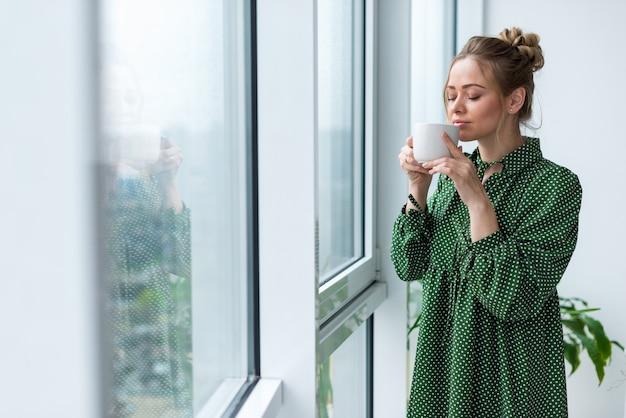 Jeune femme blonde se tient dans la salle tenant une tasse et sentant aromat de boisson Photo Premium