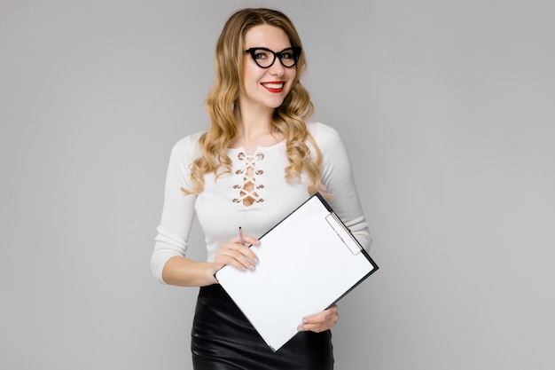 Jeune femme blonde séduisante en vêtements noir et blanc souriant montrant le presse-papiers dans ses mains, debout dans le bureau sur fond gris Photo Premium