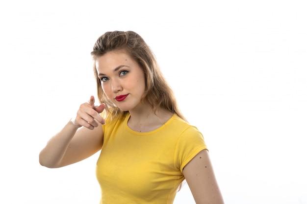 Jeune Femme Blonde Avec Un T-shirt Jaune Pointant Photo gratuit