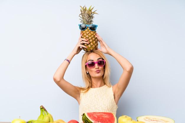 Jeune femme blonde tenant un ananas avec des lunettes de soleil Photo Premium
