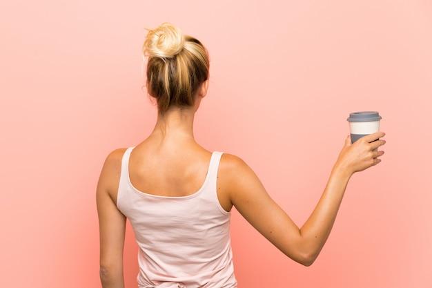 Jeune femme blonde tenant un café à emporter en position arrière Photo Premium