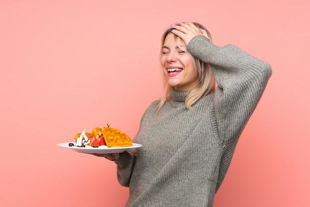 Jeune Femme Blonde Tenant Des Gaufres Sur Un Mur Rose Isolé A Réalisé Quelque Chose Et A L'intention De La Solution Photo Premium