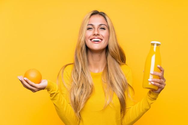 Jeune Femme Blonde Tenant Un Jus D'orange Photo Premium