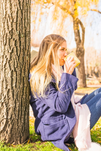 Jeune femme, boire, sous, arbre, dans, automne, parc Photo gratuit